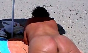 BBW wife takes sun bath on the nude beach exposing her greasy booty